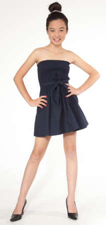 Teen asian girl posing in a black dress and heels photo