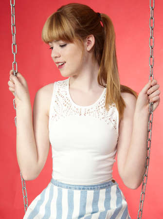 Attractive blond teen girl portrait on a swing