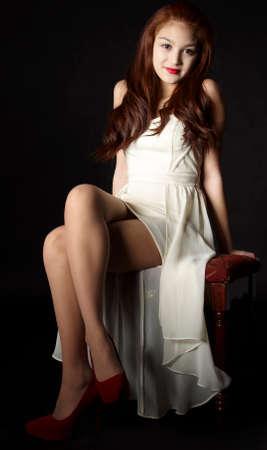 pantimedias: Modelo de la muchacha de piernas largas que se sienta con las piernas cruzadas Foto de archivo