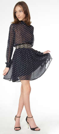 Teen model posing in a short black dress and high heels