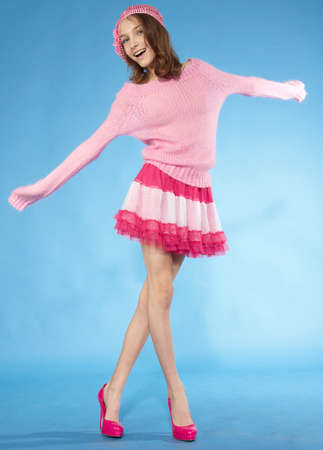Happy and carefree teen model posing Pink skirt and sweater against a blue background photo