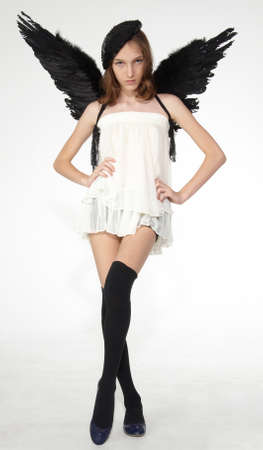 Teen model posing wearing black feather wings and stockings