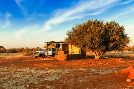 Pickup 4x4 car with a tent on the roof on road trip has a stop at a camping rest area in desolate nature landscape in the desert of Kalahari in Namibia, Africa Editorial