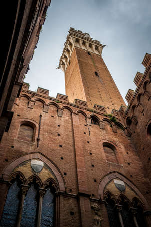 the Mangia Tower, Torre del Mangia, view from the courtyard of the adjacent the Public Palace, Palazzo Pubblico, the city hall 免版税图像
