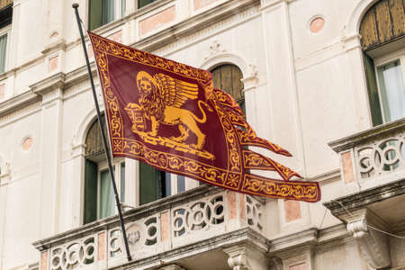 Flag of Venice with winged lion and old Venetian building on background. Cloudy winter day.