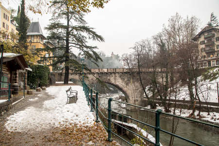 Roman bridge (ponte romano - Römerbrücke) on the promenade with snow in winter in Merano South Tyrol Italy