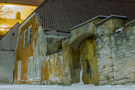 Wall and historic wooden gate on Tallinn Old Town street in winter at night. Estonia