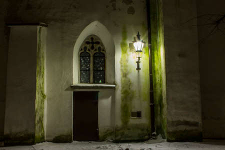 The door and window on the historic wall of Cathedral of Saint Mary the Virgin in Tallinn at night. Estonia