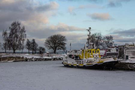 A tugboat frozen in the sea near a pier in Tallinn. Estonia