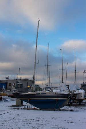 Wooden sailing yacht on shore at the Flight Harbor Museum in Tallinn in winter. Estonia