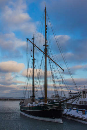 Historic sailing ship frozen in the water near the pier in Tallinn. Estonia