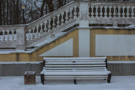Snowfall in Tallinn. Wooden bench near the stairs in a snow-covered garden. Estonia 版權商用圖片