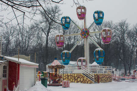 Snowfall in Tallinn. Childrens Ferris wheel in a snow-covered park. Estonia