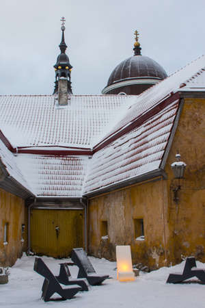 Courtyard in Tallinns Old Town in winter. Snow-covered tiled roof, church dome. Estonia 版權商用圖片