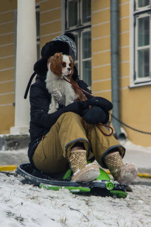 The girl with her dog rides on a sled in a hill in Tallinn. Estonia