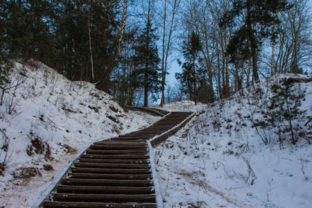 Wooden stairs leading to the snowy Hill of the Three Crosses in Vilnius at dawn. Lithuania