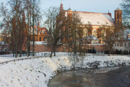 View of the Church of St. Francis and Bernard near the river Vilnia in the Old Town of Vilnius in winter. Lithuania