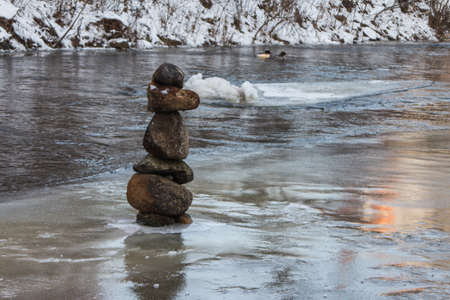 Balanced stone pyramid in the middle of the river Vilnia in Vilnius in winter. Lithuania