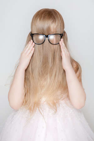 her: Little girl playing with her long hair. Shes hiding her face and trying to wear glasses
