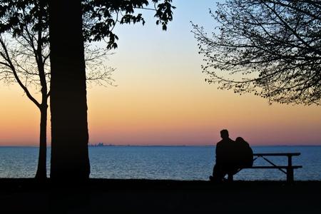 Silhouette of hugging couple watching the sun set over the lake  Beautiful orange glow