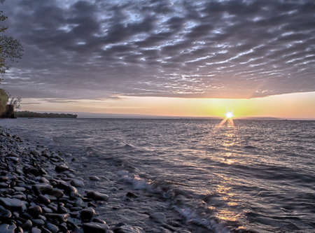 Picturesque beauty of sun setting over lake  Rock covered beach glistens  Heavy blanket of clouds hangs over