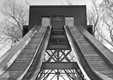 Black and white of a sled shute  Metal beams criss cross underneath   Stock Photo