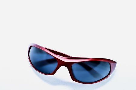 Sleek red plastic sunglasses with dark non reflective lens  Room for text
