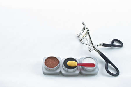 Three eye shadow containers, applicator, and eye lash curler  Stock Photo