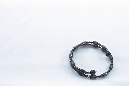 Jewelry composed of dark metallic stones and red beads  Stock Photo