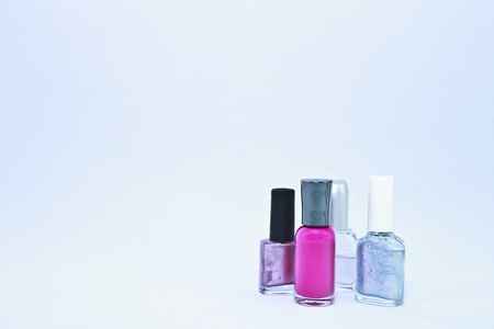 Four different nail polish jars  Varying sizes, colors and styles including hot pink metallic and clear  photo