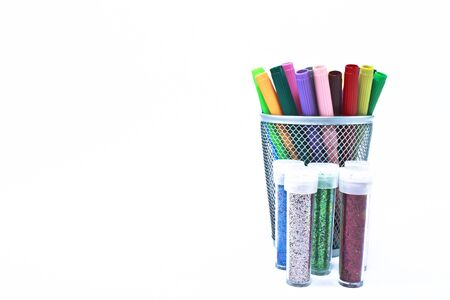 Metal container with a multitude of colored markers propped inside, including every shade of the rainbow. Containers of colored glitter are positioned close by.