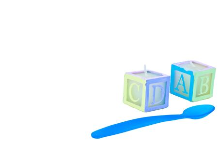 ABC block candles with a blue baby spoon, all on white with plenty of room for text. Stock Photo