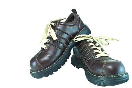 Pair of thick rubber-soled, brown leather shoes with fat laces  One is propped against the other, on white