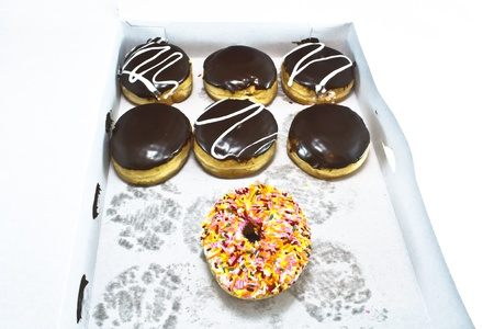Box of many uninspiring chocolate frosted donuts. One colorful rainbow sprinkle donut stands out.  Stock Photo