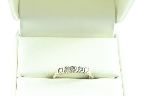 Modest ring with five small inlaid diamonds in a gold band  White leather ring case