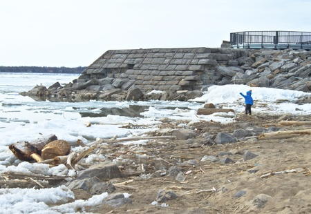 Toddler playing on the cold icy shoreline  He is dressed in a blue hooded sweatshirt  He is throwing stones into the water   photo