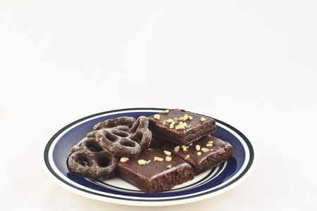 Chocolate-covered pretzels and walnut-covered fudge brownie squares on a white and blue plate