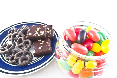 Plate of chocolate-covered pretzels and walnut-covered fudge brownie squares  Jar of multi-colored jelly beans  Stock Photo