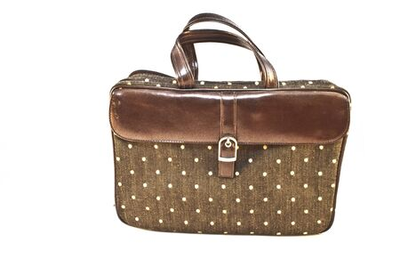 A stylish purse on white  The purse has brown leather strap and buckle  There are small dots on the cloth body