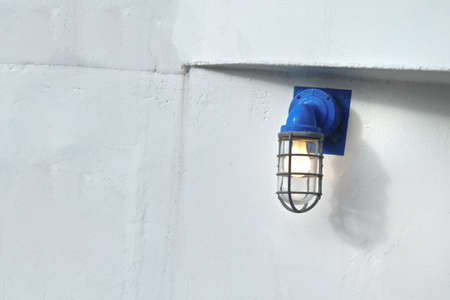 Yellow shining light bulb with a safety blue base and protective cage