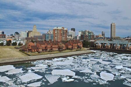 View of Buffalo in early spring  Diverse architecture sits on the coastline while giant ice chunks float by  Beautiful cloud formations appear overhead