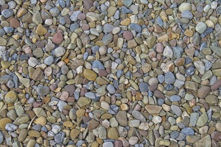 Close-up of water-worn beach stones with differing shapes, sizes, and colors. Interesting texture.