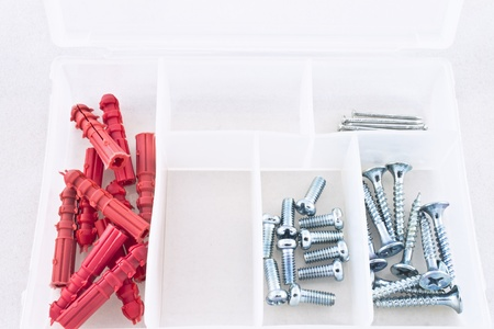 Small plastic container of nails, screws, and red plastic anchors. Stock Photo
