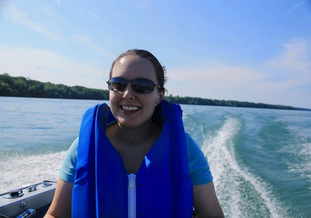 Woman with life jacket riding in a speeding boat.  She is wearing sun glasses and has a smile on her face. Beautiful water and land scape are seen behind her.