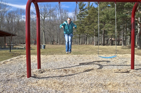 Woman on swing set having fun at the park. She is in mid swing with feet pointed downward.