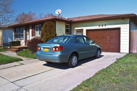 reasonable: Modest one story ranch style home with compact car in the driveway.