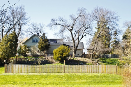 Beautiful country home surrounded by trees. This residence sits on a hill and is surrounded by trees. A wooden fence surrounds the perimeter of the backyard.  Stock Photo - 19249314
