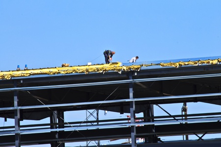 Two men are tethered to the roof of a high-story building. They are working on the roof of this new building under construction. Metal beams and rafters make up the skeleton of this structure.  Stock Photo