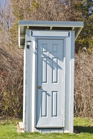 latrine: Newly constructed outhouse with gray door and white paneling.