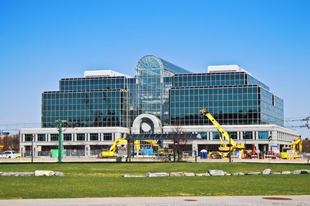 Mirrored glass building in downtown Buffalo. There is a brilliant blue sky behind it and construction machinery in the front.  Stock Photo